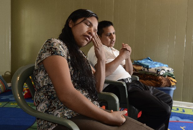 Domitina Mendez wipes away tears as her husband, Ovidio Mendez, discusses their efforts to regain custody of their five children.