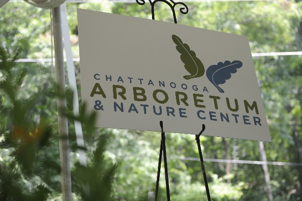 The sign of the newly combined Chattanooga Nature Center and the Reflection Riding Arboretum & Botanical Garden stands inside the tent for the celebration party. They are merging into the Chattanooga Arboretum & Nature Center.