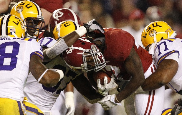 In this Nov. 5, 2011, file photo, Alabama running back Eddie Lacy (42) is tackled by LSU linebacker Karnell Hatcher (37) and defensive tackle Josh Downs (77) during the first half of an NCAA college football game in Tuscaloosa, Ala.