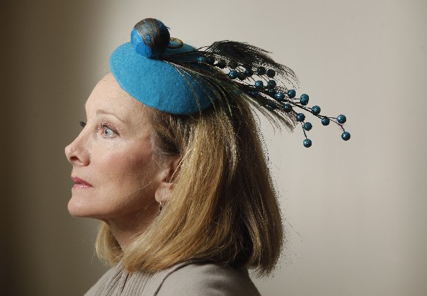 Lynn Alsobrook models one of her hats, the Peacock Fantasy, at the home of Lisa Maclellan on Lookout Mountain on Tuesday afternoon. Alsobrook has been making the small hats for about six months now.