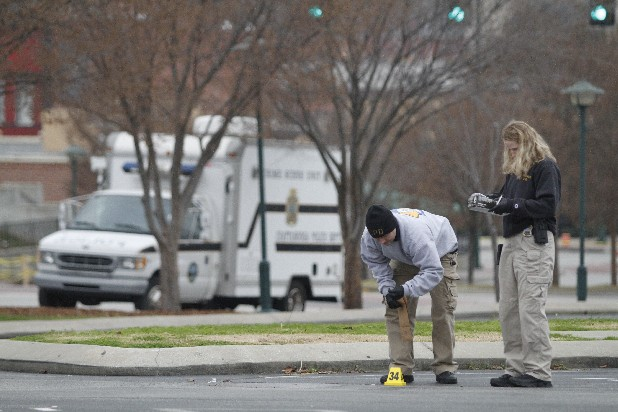 Investigators William Salyers and Heather Williams collect a bullet casing on Sunday as evidence from a shooting in a parking lot at the corner of 4th and Cherry Streets in downtown Chattanooga. The shooting happened around midnight on Christmas Eve leaving nine people wounded.