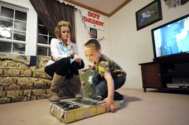 Bethany Miller, 27, watches as her son, Tanner, 3, gets excited about his dad's Christmas presents at their home in Trenton, Ga. Sgt. Chris Miller is scheduled to arrive in early January from a second tour of duty in Iraq.