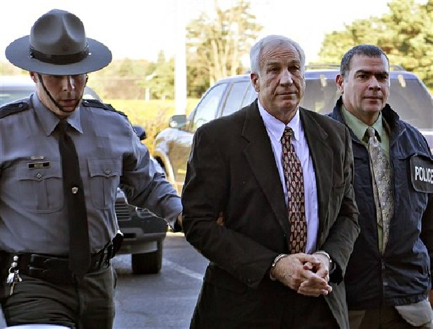 "Former Penn State football defensive coordinator Gerald ""Jerry"" Sandusky, center, arrives in handcuffs at the office of Centre County Magisterial District Judge Leslie A. Dutchcot while being escorted by Pennsylvania State Police and Attorney General's Office officials in State College, Pa. Former board members of Jerry Sandusky's  charity say its CEO never told them about a 2002 shower incident that is the focus of child sexual abuse charges against the retired Penn State assistant coach."