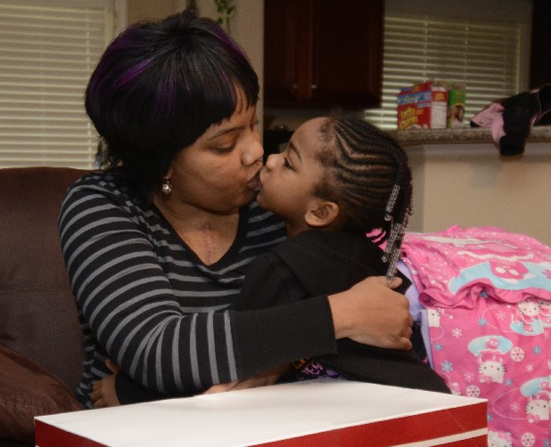 Miracle McIntosh, left, gets a kiss from daughter Zoei Granger during a reunion Friday in their Harrison home. McIntosh had been at Vanderbilt since mid-November for a heart transplant and follow-up treatment.