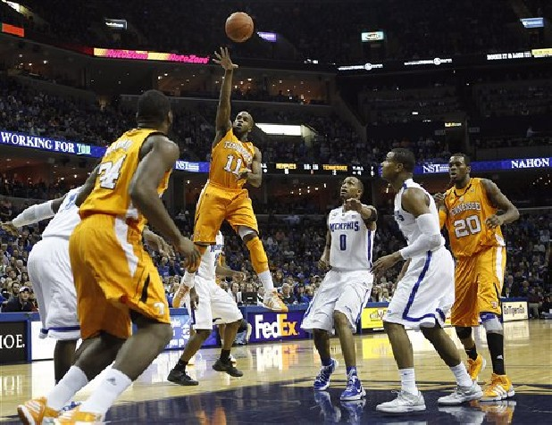Tennessee guard Trae Golden (11) goes to the basket against Memphis defenders Chris Crawford, right, and Ferrakohn Hall (0) in the first half of an NCAA college basketball game on Wednesday, Jan. 4, 2012, in Memphis, Tenn.