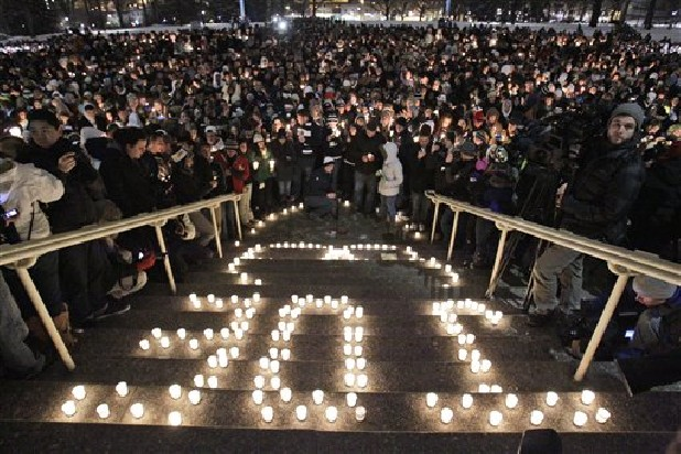 A candle light memorial honoring legendary football coach Joe Paterno, who died Sunday morning, Jan. 22, 2012, is held on the lawn in front of Old Main the Penn State University campus Sunday, Jan. 22, 2012 in State College,Pa.