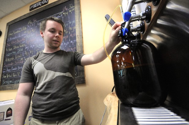 David Hilleke pulls draft beer for customer Paul Lundberg Monday at Beverage World in Fort Oglethorpe. The business is seeking approval that would allow people to sample small amounts of beer before they buy.