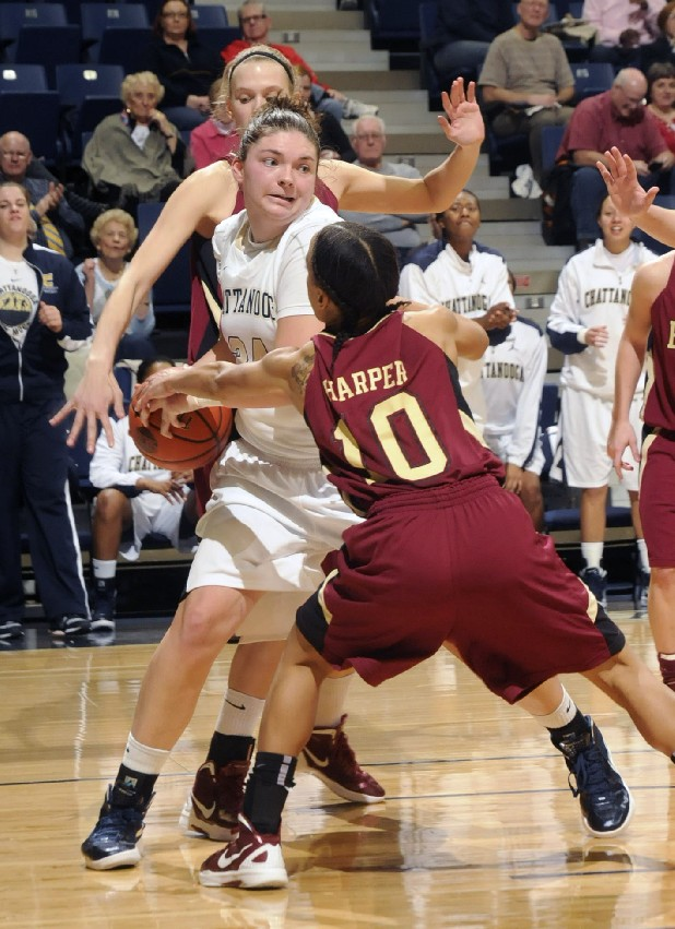 Faith Dupree of UTC is pressured by Elon defenders Monday at McKenzie Arena.