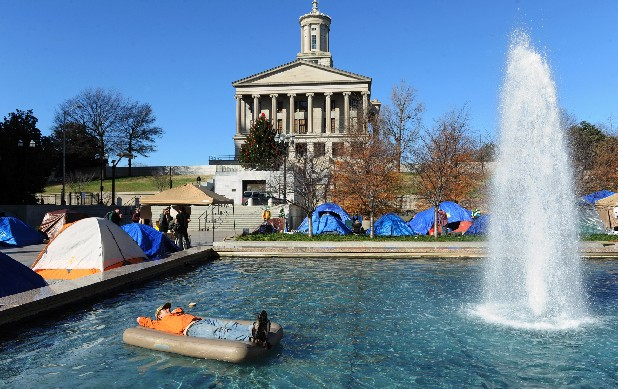 Occupy Nashville protestor Duncan McAfee relaxes on an air mattress after checking it for leaks in a fountain at Legislative Plaza in Nashville, Tenn. Sunday, Dec. 25, 2011. Between 80 to 100 Occupy Nashville protestors spent the night on Christmas Eve.