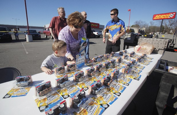 Wyatt Poteet, 3, looks over miniature versions of monster trucks with Sheila Parsons on Thursday. The Advanced Auto Parts store in Ringgold, Ga., celebrated the business's remodeling with a meet-and-greet with the Stonecrusher monster truck and its driver, Morgan Kane. The store was one of three locations showing off the trucks.