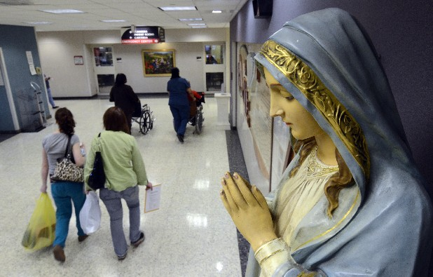 People walk past  a statue of the Virgin Mary at Memorial Hospital.