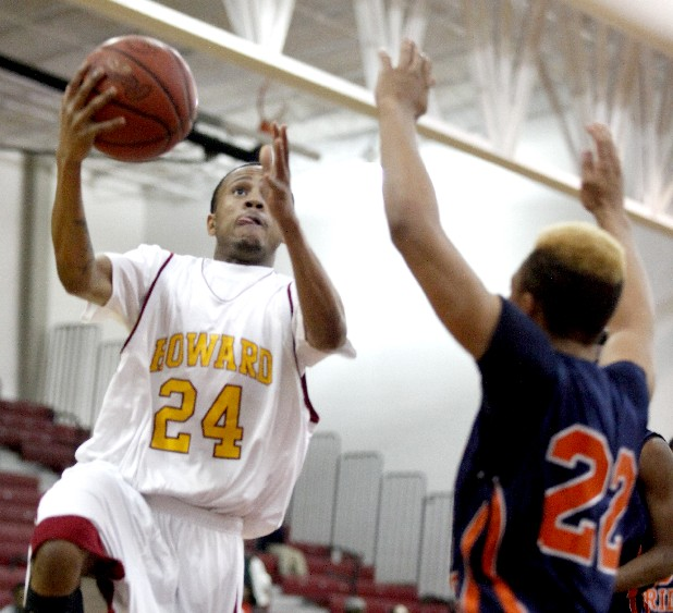 Howard basketball player RodDarius Martin, left, lays the ball up past East Ridge High School's Eddie Hitchcock during a game at Howard on Tuesday night.