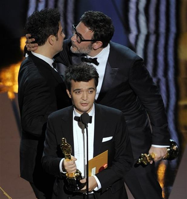 "Best director winner Michel Hazanavicius, right, embraces Ludovic Bource, winner of best original score as producer Thomas Langmann, center, speaks after accepting the Oscar for best picture for ""The Artist"" during the 84th Academy Awards on Sunday, Feb. 26, 2012, in the Hollywood section of Los Angeles. The film won a total of five Oscars."