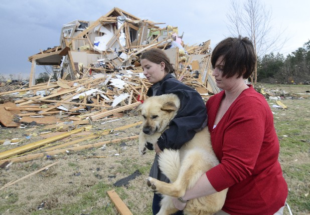 Lisa Copeland, right, and Kacie Rose carry a dog to a safe place before a second round of storms approaches Friday afternoon Savannah Hills Drive near Kitrell Lane.