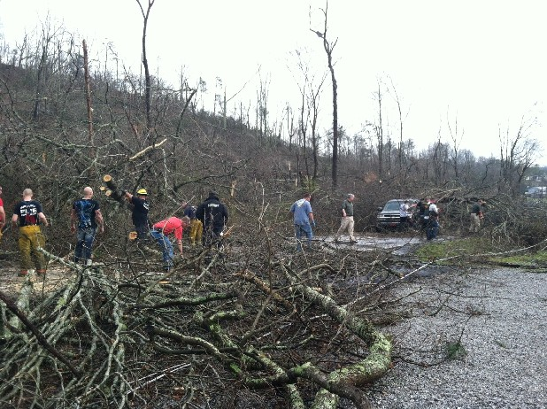 Residents clear downed trees from a road in the Harrison area.