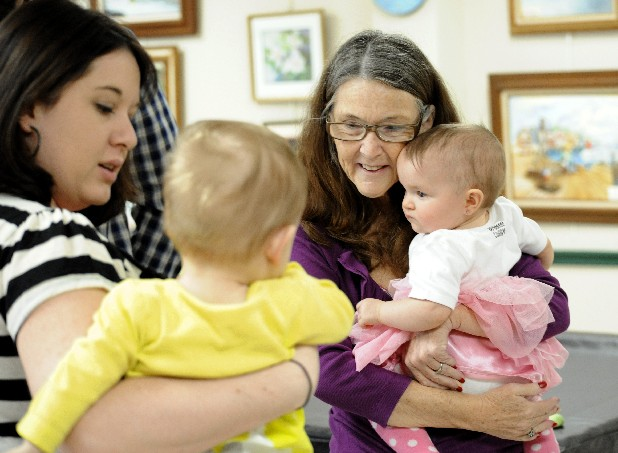 Yvonne Burroughs holds her granddaughter, Cheyenne Douglas, as she visits with Brielle Barnes and her mom, Nicole, Saturday at Cheyenne's first birthday party held at the East Ridge Community Center. Cheyenne and Brielle were both premature babies.