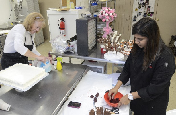 Patti Taylor, left, and Nichelle Patel work Thursday at the Cake Boutique.