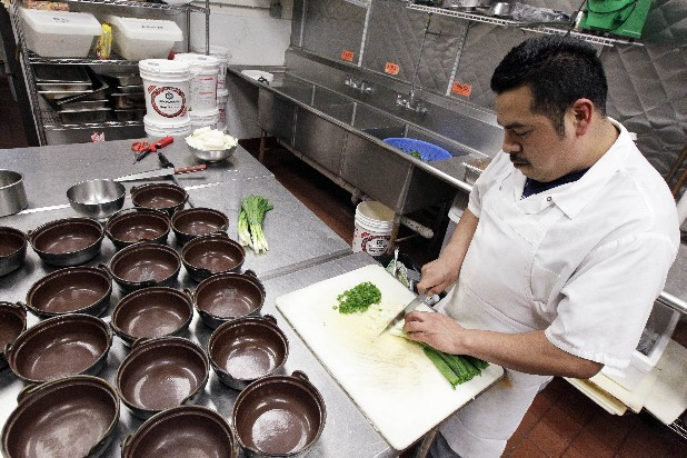 Gilberto Hernandez Garcia prepares scallions at Woori Village restaurant in Chicago. The U.S. economy is improving faster than economists had expected. They now foresee stronger growth and hiring than they did two months earlier — trends that would help President Barack Obama's re-election hopes.