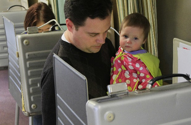 Marc Lewis holds daughter Alexa, nine-months-old, as he votes at the Heritage Universalist Unitarian Church today in Cincinnati. Ohio is the biggest prize in political significance on Super Tuesday, the GOP presidential primary showdown across 10 states for more than 400 delegates. Mitt Romney and Rick Santorum have devoted much of their campaign attention to Ohio in recent days. (AP Photo/Al Behrman)
