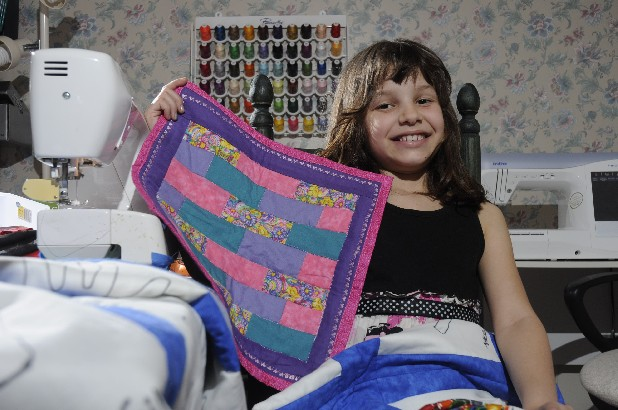 Maddie Gilley, 7, made her first quilt, above, earlier this year. She wants to auction her second one to raise money for her school's Parent Teacher Organization.