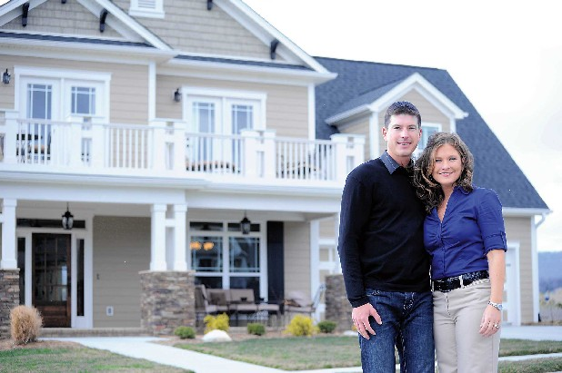 Brian and Amy Hager stand in front of their newly finished home Saturday afternoon on Hearthstone Circle in the Overlook subdivision. The Hagers moved into the home this past June.