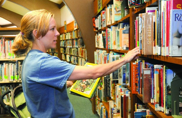 Cayce Weekley browses the children's section at the Northgate Library.