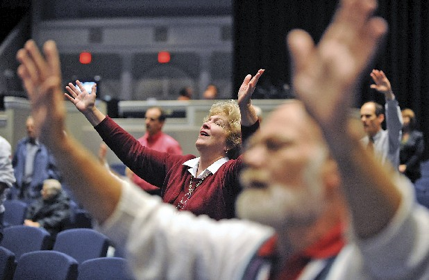 Donna Camarata, center, and Geoffrey Whitehead, front right, raise their hands in worship to the song, How Great it Our God, during a service at Abba's House in this file photo.