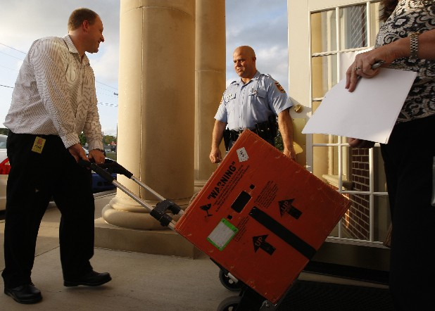 An FDIC employee wheels a box past Georgia State Trooper Tony Rathel, who was providing security, and into the Covenant Bank & Trust building in Rock Spring, Ga. State regulators shut down the bank, and it reopened as a branch of Stearns Bank.