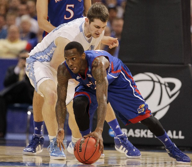 Kansas guard Tyshawn Taylor chases a loose ball against North Carolina forward Tyler Zeller, left, during the first half of the NCAA men's college basketball tournament Midwest Regional final today in St. Louis. (AP Photo/Jeff Roberson)