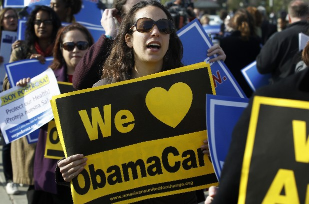 Supporters of health care reform stand in front of the U.S. Supreme Court in Washington on Wednesday, the final day of arguments regarding the health care law signed by President Barack Obama.