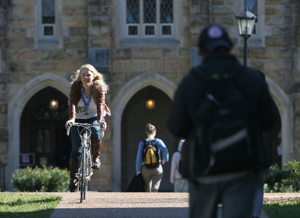 Carrie Ryan, a student at Sewanee University, rides her bike to class past Dupont Library in this file photo.
