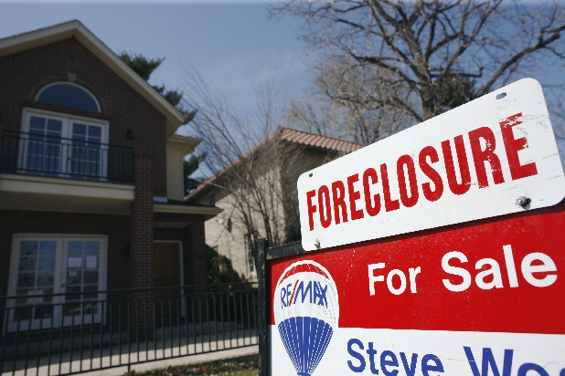 A foreclosure sign sits atop a for sale sign in front of a single-family home in Denver.