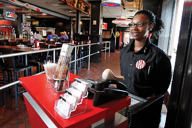 Britney Bledsoe, a hostess of three years at the downtown Chattanooga TGI Friday's restaurant, waits for customers to arrive during lunch hour.