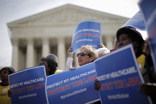 In this March 28, 2012 file photo, supporters of health care reform rally in front of the Supreme Court in Washington on the final day of arguments regarding the health care law signed by President Barack Obama. Arguments in the Supreme Court failed to yield clear hints how the justices would rule on the question of whether President Barack Obama's health care overhaul would be left standing if the high court were to strike down the linchpin provision that all Americans must have health insurance. (AP Photo/Charles Dharapak, File)