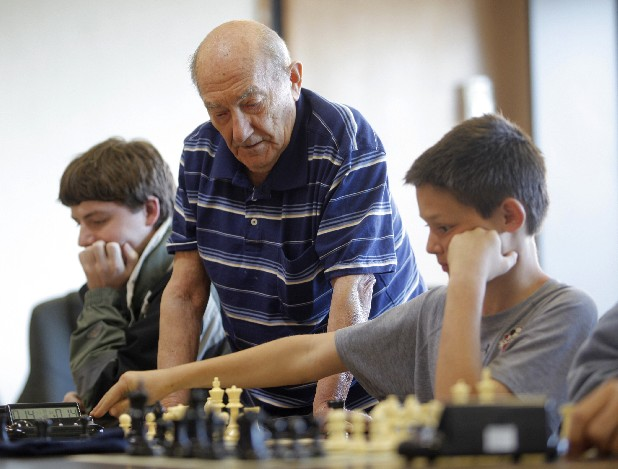 Stephen Wills, left, and Jack Beaty, 11, play chess under the watchful eye of Sasha Lokshin, center. The Chattanooga Chess Club meets for a weekly playing session at the downtown YMCA.