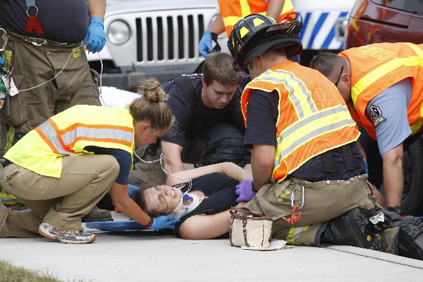 A woman is loaded onto a stretcher by paramedics on the sidewalk near the Red Bank City Hall on Dayton Boulevard today after a red Mercury Villager  rear-ended a school bus carrying Red Bank High School and Middle School students. No students were injured, but paramedics said the driver and passenger from the van were taken to the hospital after complaining of injuries.