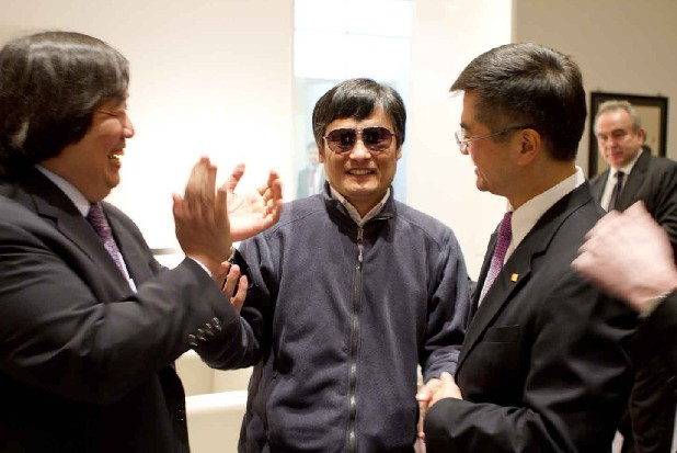 In this photo released by the US Embassy Beijing Press Office, blind lawyer Chen Guangcheng, center, holds hands with U.S. Ambassador to China Gary Locke, right, as U.S. State Department Legal Advisor Harold Koh, left, applauds, before leaving the U.S. embassy for a hospital in Beijing Wednesday May 2, 2012. (AP Photo/US Embassy Beijing Press Office, HO)