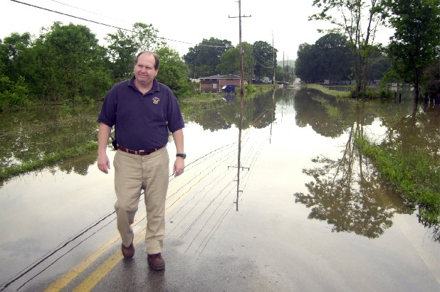 David Ashburn inspects flood waters along Glentana Street in Rossville, Ga. in this file photo.