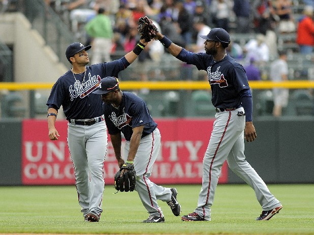 Atlanta Braves  left fielder Martin Prado, Michael Bourn, center, and Jason Heyward right, celebrate a 7-2 victory over the Colorado Rockies during a baseball game Sunday, May 6, 2012, in Denver. (AP Photo/Jack Dempsey)