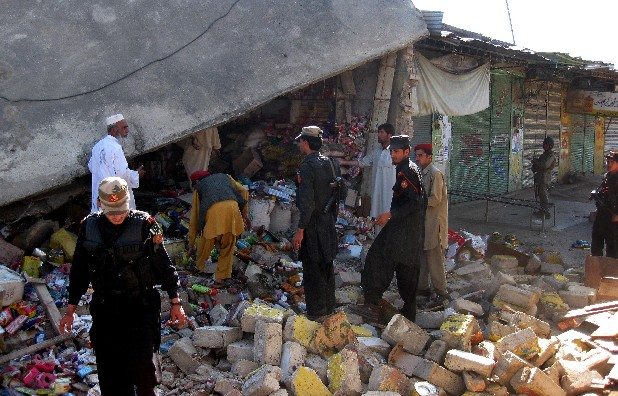 Pakistani security personnel visit the site of a suicide bombing in the Pakistani tribal region of Khar in Bajur on Friday, May 4, 2012. A suicide bombing in a Pakistani market close to the Afghan border killed 20 people Friday, officials said, a day after the U.S. released letters seized from Osama bin Laden's compound that criticized Pakistani militants for killing too many civilians. . (AP Photo/Anwarullah Khan)