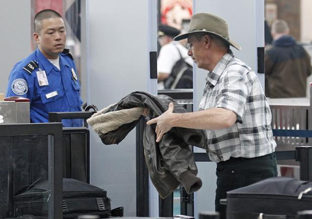 A traveler passes through a security check point at Portland International Airport in Portland, Ore. Airport security procedures, with their intrusive pat downs and body scans, don't need to be toughened despite the discovery of a new al-Qaida airline bomb plot using more sophisticated technology than an earlier attempt, congressional and security officials said Tuesday.