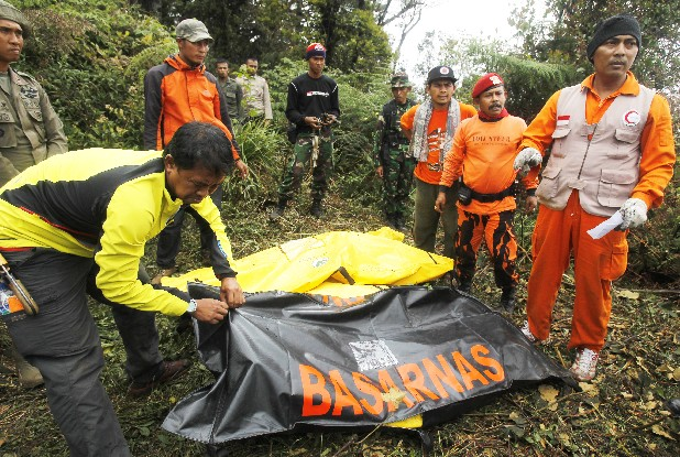 Indonesian rescue teams Friday close plastic covers over the bodies of victims after a Sukhoi Superjet-100 plane crashed at mount Salak in Bogor, Indonesia. The crash of a Russian-made passenger jet into the flanks of an Indonesian volcano has put a spotlight on the notoriously informal atmosphere aboard new aircraft during manufacturer demonstrations.