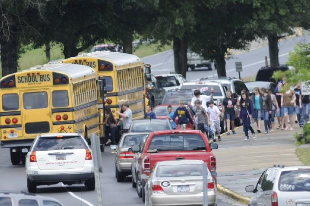 Northwest Whitfield students prepare to board a bus after school Monday. North Georgia schools will cut their budgets for the 2012-13 school years.