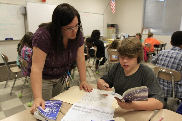 Jessica Holloway works with Thomas Grider on reading comprehension during class Thursday morning at Hixson Middle School. Holloway received $1,000 from UNUM's Strong Schools Grant Program which she used to purchase books that the students are currently reading.