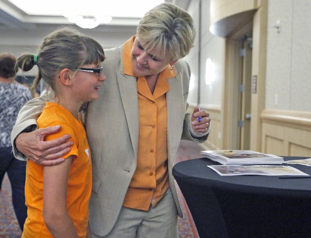 Maren Gwaltney, left, gets a hug from University of Tennessee women's basketball coach Holly Warlick during the UT Caravan on Wednesday.  Warlick was a guest on the caravan along with UT athletic director Dave Hart, football coach Derek Dooley and men's basketball coach Cuonzo Martin.
