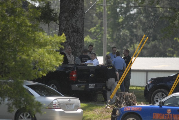 Police gather outside a home today on Lower Dawnville Road in Whitfield County. A double homicide was discovered by neighbors early this morning at 1200 Green Springs Road nearby.