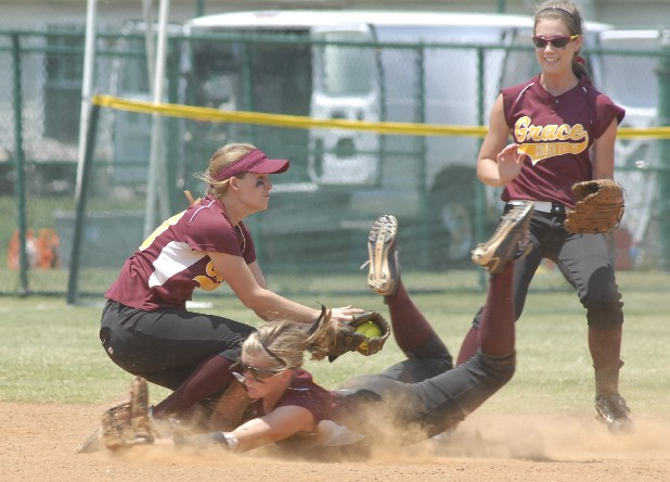 Grace Academy's shortstop, Kaitlyn Eldridge collides with center-fielder Bethany Cowart as Eldridge catches the final out of the Lady Golden Eagles' state championship win over Decatur County Riverside High School.