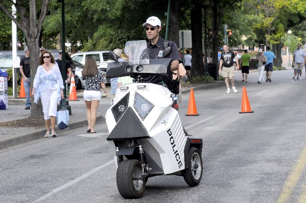 Chattanooga Police Lt. Eric Tucker rides one of three PMV (personal motorized vehicles) being used at Riverbend 2012. Lt. Tucker approaches the main entrance at Chestnut Street and Second.