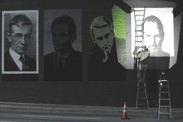 Kevin Bate, a Chattanooga muralist, uses a projector to display the face of deceased Apple CEO, Steve Jobs, onto a building off of Frazier Avenue in this file photo.