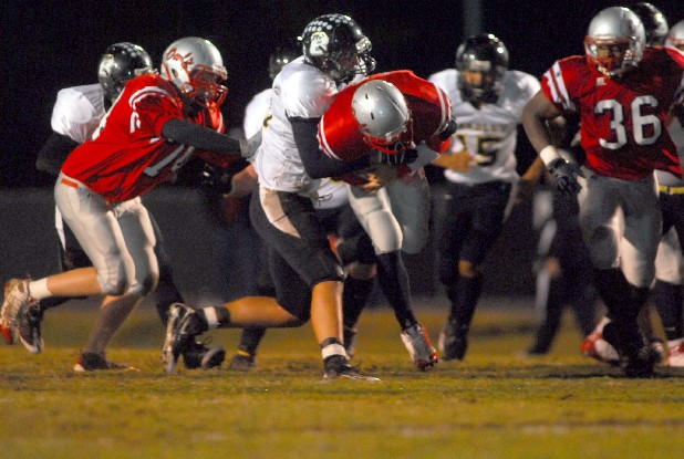 Quarterback Brady Reed, 17, of Ooltewah High School attempts to run through Bradley Central defense during a game at Ooltewah High School.